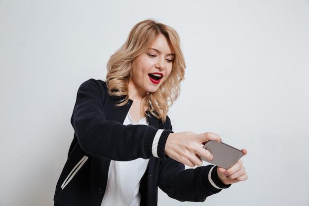 Портрет случайный подростковой молодой женщины, играя на мобильном телефоне