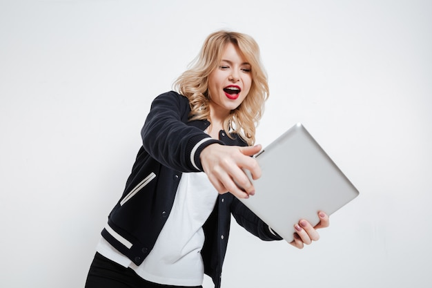 タブレットコンピューターでゲームをプレイして興奮している若い女性の肖像画