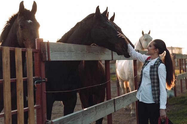 かなり若い女性が彼女の馬の世話をします。
