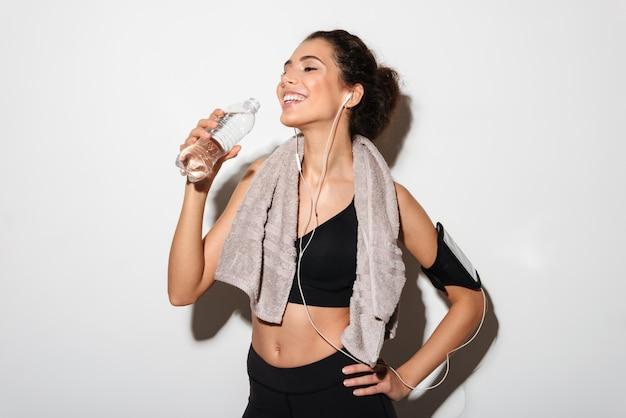 Счастливая женщина фитнеса брюнет с полотенцем держа руку на бедре