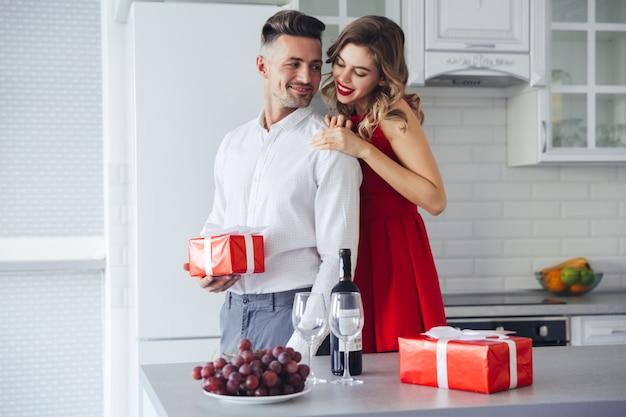 Юная леди обнимает и смотрит на своего мужчину, который держит настоящий момент дома, концепция дня святого валентина
