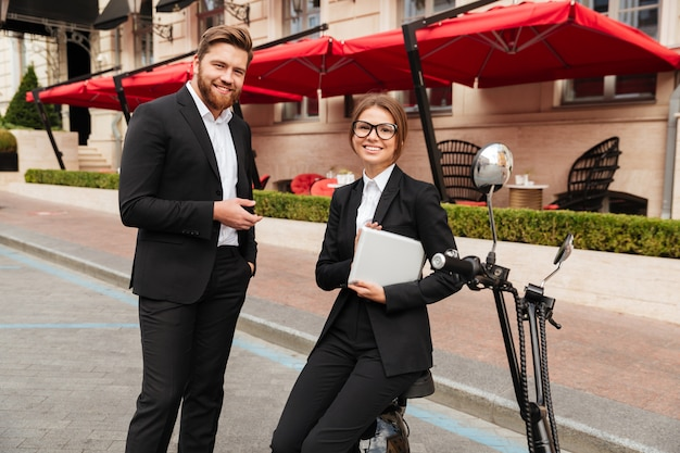 Счастливая пара бизнес позирует возле современного мотоцикла на открытом воздухе