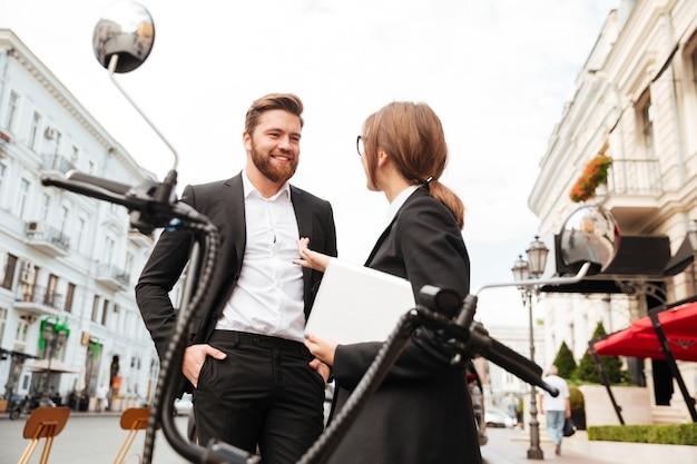Улыбаясь бизнес пара позирует возле современного мотоцикла на открытом воздухе
