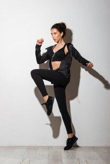 Концентрированная кудрявая брюнетка фитнес женщина