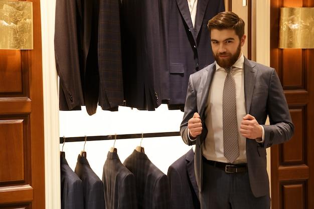 Мужчина в костюме позирует магазин