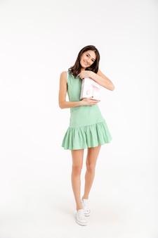 Полная длина портрет улыбающейся девушки, одетой в платье