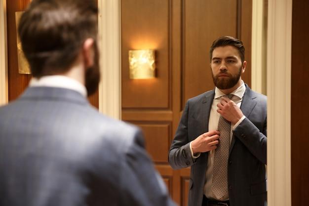 Вид со спины молодого человека, смотрящего в зеркало