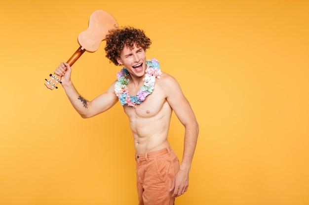 Счастливый возбужденный мужчина без рубашки держит гавайскую гитару и смотрит в сторону