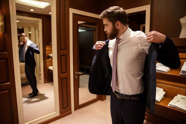 Бородатый мужчина надевает куртку