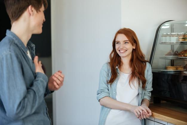 カフェで彼女の友人を見て赤毛の女性