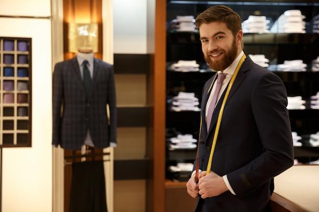 Веселый бородатый мужчина в синем костюме стоит с рулеткой в гардеробе