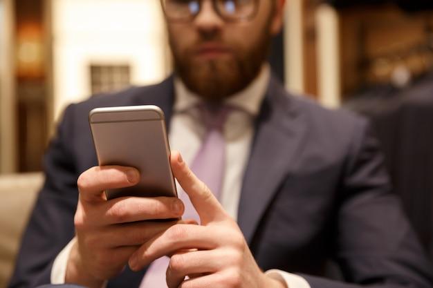 Концентрированный молодой бородатый бизнесмен в чате по телефону