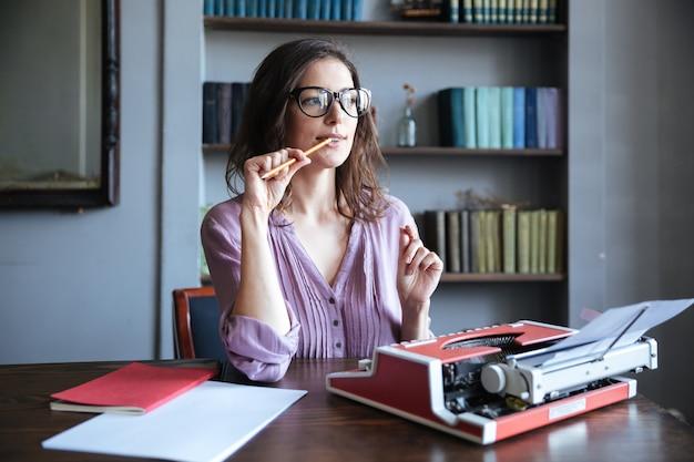座っているメガネで物思いにふける成熟した著者の肖像画
