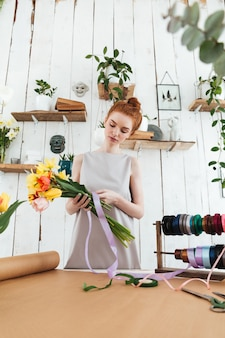 Рыжая леди флорист собирает букет, стоя возле стола