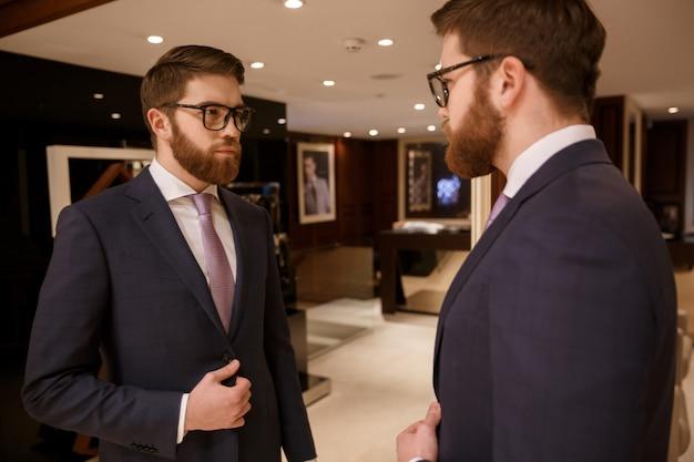 Серьезный молодой бородатый бизнесмен, стоя в помещении