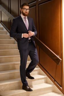 Серьезный молодой бородатый бизнесмен, стоя на лестнице в помещении