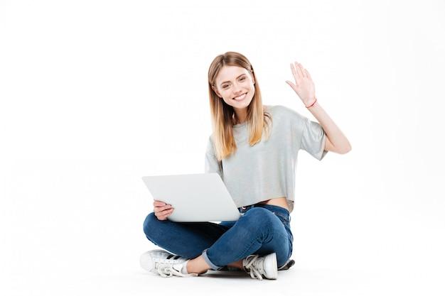 Улыбается женщина, используя портативный компьютер