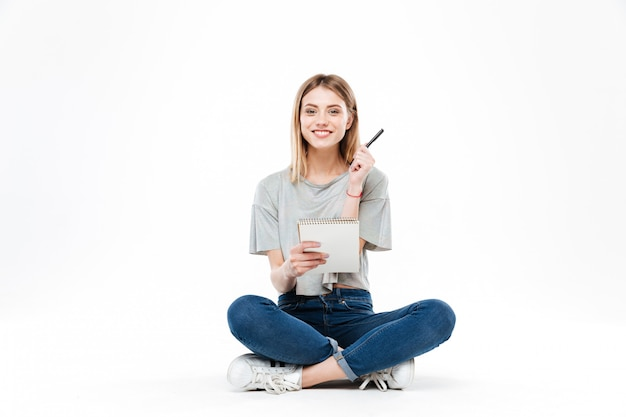 Молодая женщина, используя карандаш и тетрадь