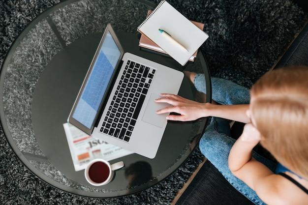 Женщина пьет чай и используя ноутбук дома