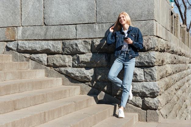 通りの階段にカジュアルな立っている身に着けている若い女性