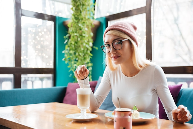 Невероятная молодая женщина ест торт и пьет кофе