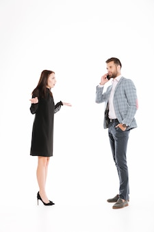 Сердитая женщина смотрит на мужчину разговаривает по телефону