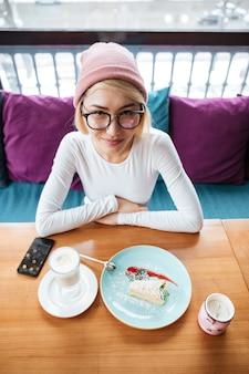Веселая молодая женщина ест торт и пьет кофе