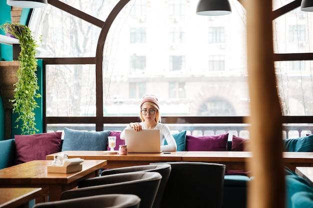 Серьезная молодая женщина сидит и использует ноутбук в кафе
