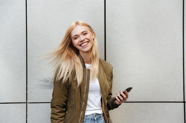 Жизнерадостная женщина с смартфон смеется