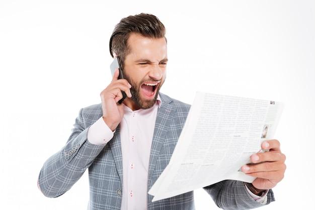 Кричать молодой человек, держащий газету и говорить по телефону.