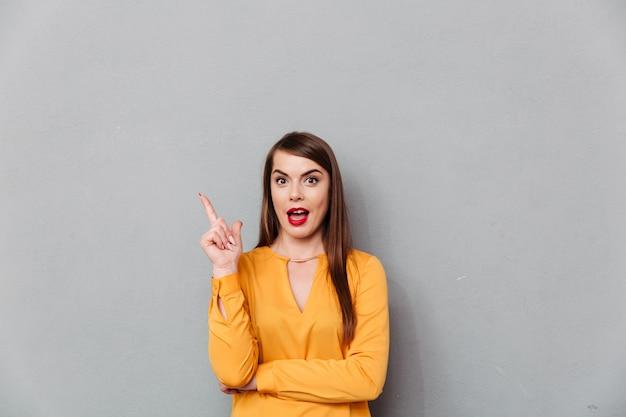 Портрет взволнованная женщина, указывая пальцем