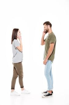 電話で話している幸せな若い夫婦。