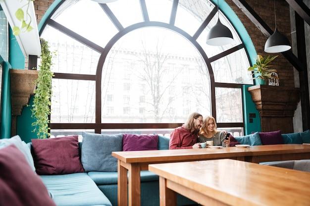 Влюбленная пара, сидя в кафе, пить кофе и с помощью телефона.