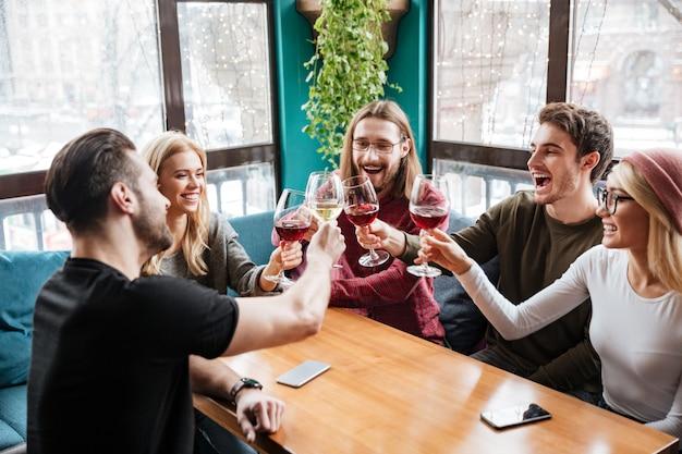 Друзья сидят в кафе и пьют алкоголь.