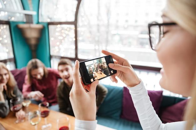 魅力的な友達がカフェに座って、電話で写真を作る。