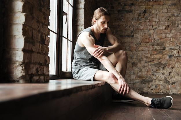 Портрет фитнес-мужчина страдает от боли в ногах