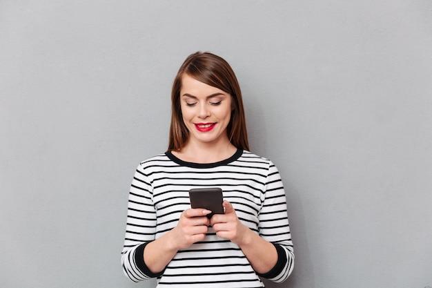 携帯電話で笑顔の女性のテキストメッセージの肖像画