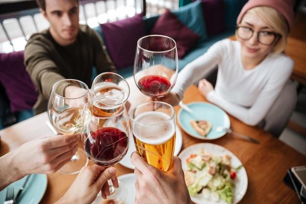 Подрезанное изображение друзей сидя в кафе выпивая спирт.