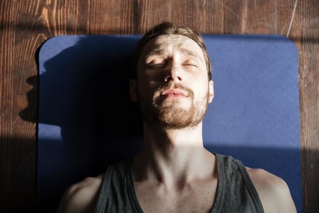 Концентрированный молодой сильный спортсмен в тренажерном зале лежит на полу