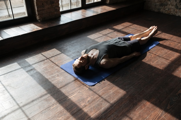 Красивый молодой сильный спортсмен в тренажерном зале лежит на полу