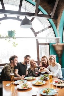Друзья сидят в кафе и с помощью мобильного телефона.