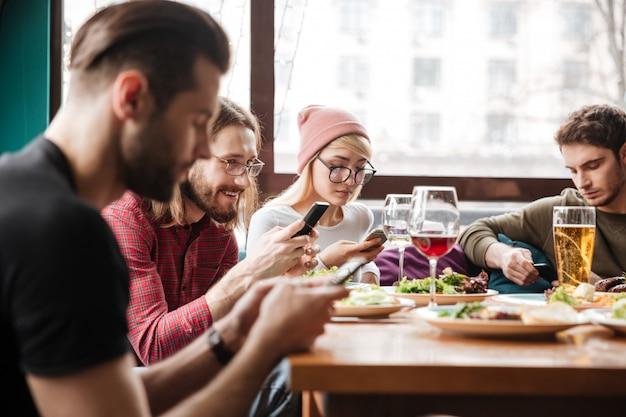 Счастливые друзья, сидя в кафе и с помощью мобильных телефонов.