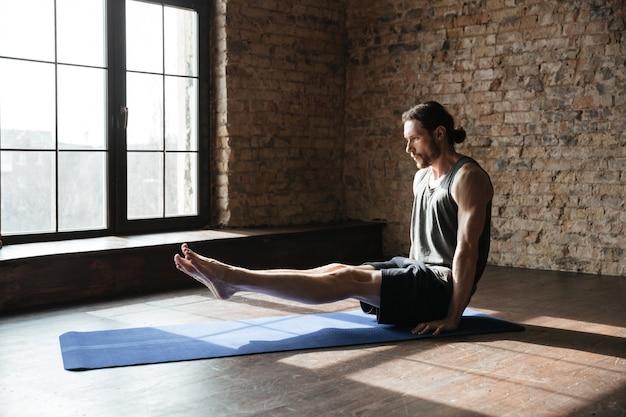 ジムで集中して強いスポーツマンはヨガスポーツの練習をします
