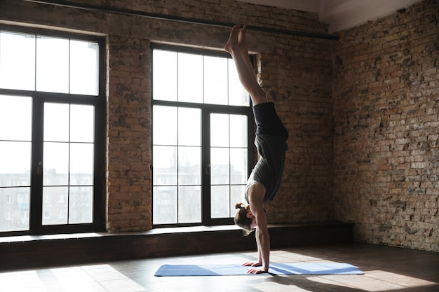 Привлекательный сильный спортсмен в спортзале делает упражнения йоги