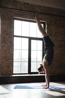 Красивый сильный спортсмен в спортзале делает упражнения йоги
