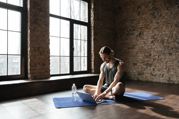 Красивый сильный спортсмен сидит возле бутылки воды, используя ноутбук