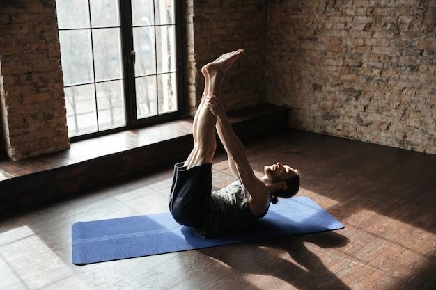 Сконцентрированный сильный спортсмен в спортзале делает упражнения йоги