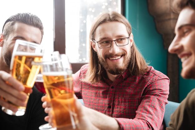 Молодые счастливые друзья сидя в кафе пока выпивающ спирт.