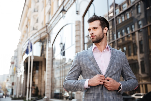彼のジャケットにボタンを押す若いハンサムな男の肖像