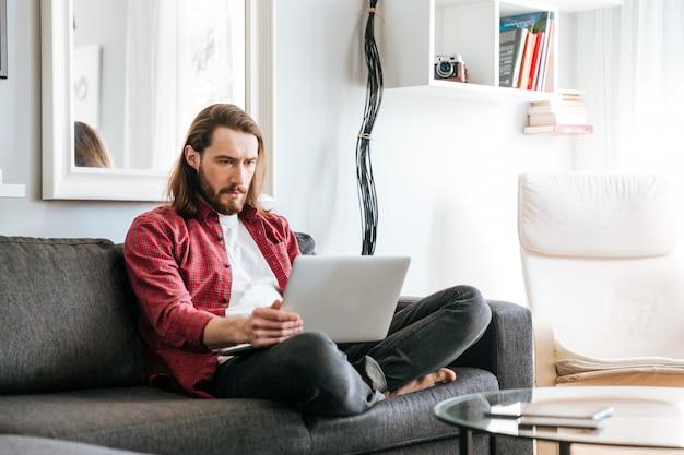 Серьезный человек сидит и с помощью ноутбука на диване у себя дома